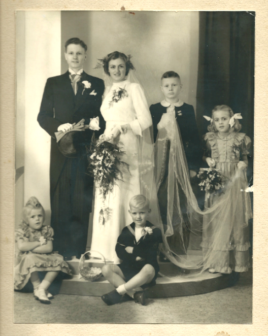 Silk satin, organza. The wedding gown and bridesmaids dresses were made by my grandmother. On the picture: my parents, the wedding couple, behind them my uncle Alexander and aunt Jeanne, in front my auntie Pauline and uncle Ron.