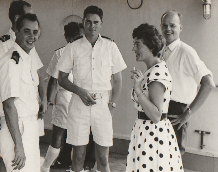 I see my young beautiful mother standing on the deck of a military ship. She is wearing a white summer dress with black dots. She laughs, she is happy.